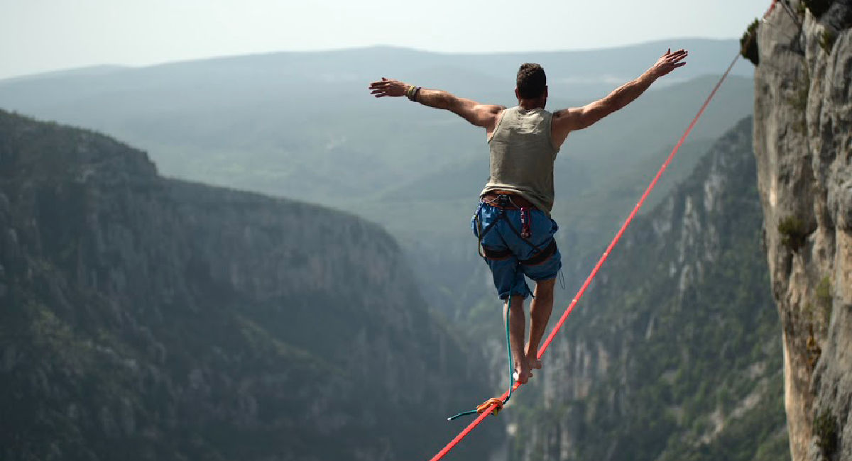 Man balancing on rope high in mountains